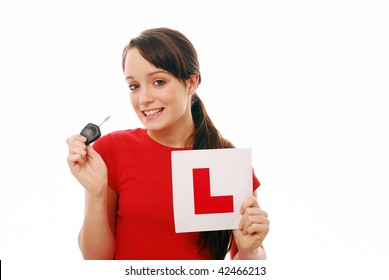 Happy teenager holding car key and L plate after passing test