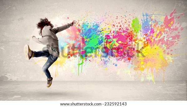 Happy Teenager springt mit buntem Tintenfleck auf städtischem Hintergrund