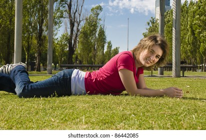 Happy teenager lying on the grass, smiling in the sun.
