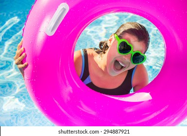 happy teenager playing on a buoy in a pool with sunglasses