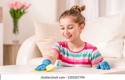 Happy teenager in rubber gloves cleaning white table in living room
