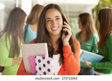 Happy teenager student on the phone with books