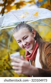 Happy teenager with umbrella making selfie in autumn park