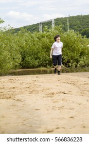 Happy teenager in white t-shirt runs on a sandy beach on a summer day.