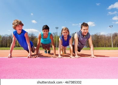 Happy teenagers doing push-up exercises outdoor