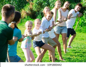 Happy teenagers with parents playing active games in summer park, tugging war