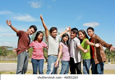 Happy teenagers in the park waving