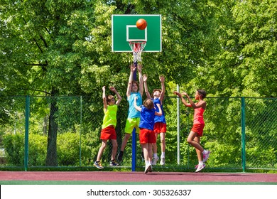 Happy teenagers playing basketball on playground