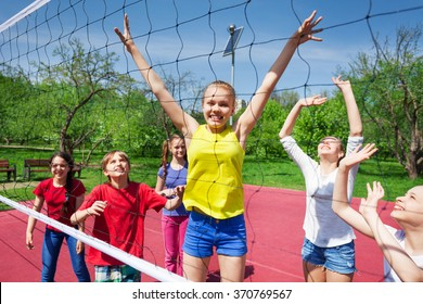 Happy teenagers playing near the volleyball net