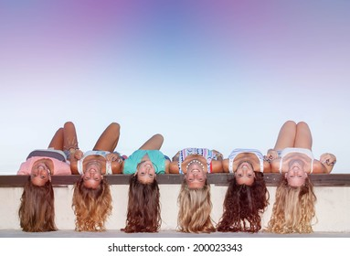 happy teens with long healthy hair laying upside down.