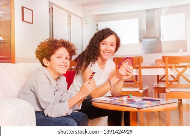 Happy teens playing card games in the living room