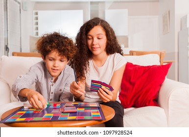 Happy teens playing table game together at home
