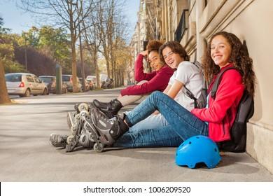 Happy teens with rollerblades sitting at sidewalk