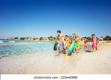 Happy teens running along sandy beach in summer