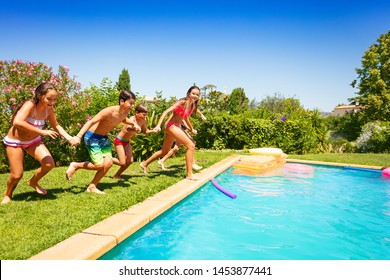 Happy teens running together to swimming pool