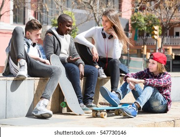 Happy teens spending time together and talking in sunny day