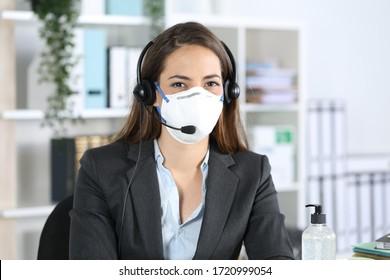 Mujer feliz medidor posando mirando la cámara evitando el covid-19 con máscaras sentadas en la oficina