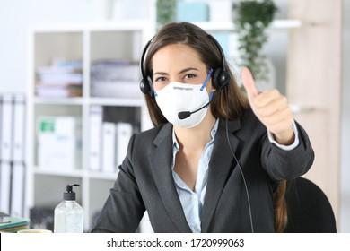 Mujer feliz del telemarketer con los pulgares hacia arriba y la cámara evitando el covid-19 con máscaras sentadas en la oficina