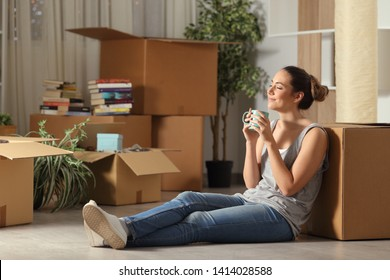 Happy tenant moving home resting breathing fresh air sitting on the floor in the night