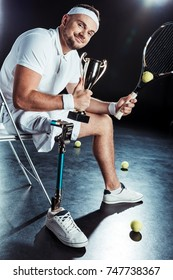 happy  tennis player with champion goblet resting on chair