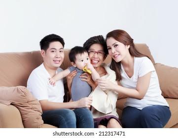 Happy Thai family sitting on the sofa