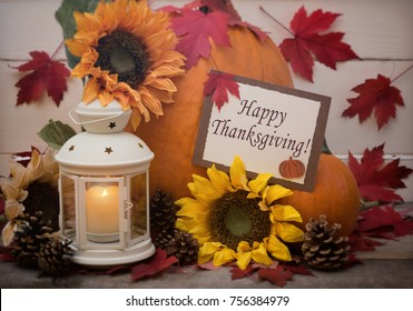 Happy Thanks giving card in Pumpkin Still Life Scene with candle, flowers, falling maple leaves with room or space for your copy, text, or design.  Horizontal with cross process and shaded vignette
