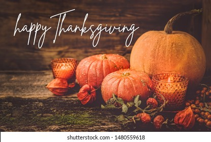 Happy thanksgiving concept. autumn still life with pumpkins, leaves and candles on wooden background. fall harvest season, thanksgiving holiday. autumn holiday card design