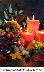Happy Thanksgiving cornucopia table setting centerpiece decorated with autumn leaves, fruit, nuts and orange burning candles, close up vertical.