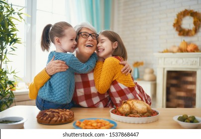 Happy Thanksgiving Day! Autumn feast. Family sitting at the table and celebrating holiday. Traditional dinner. Grandmother and granddaughters.