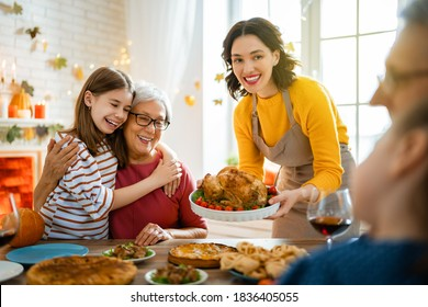 Happy Thanksgiving Day! Autumn feast. Family sitting at the table and celebrating holiday. Grandparents, mother and children. Traditional dinner.