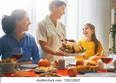 Happy Thanksgiving Day! Autumn feast. Family sitting at the table and celebrating holiday. Traditional dinner. Grandmother, mother and daughter.