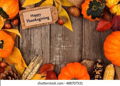 Happy Thanksgiving Gift Tag With Frame Of Colorful Leaves And Pumpkins Over A Rustic Wood Background