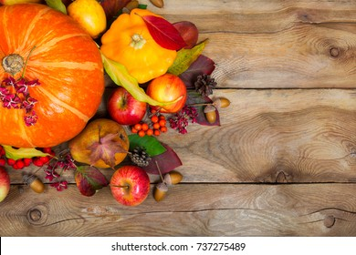Happy Thanksgiving greeting background with pumpkin, yellow squash, apples, pear, rowan berries, colorful leaves and acorns, copy space.