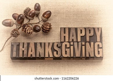 Happy Thanksgiving greeting card - word abstract in vintage letterpress wood type with acorns and cones fall decoration against burlap canvas, sepia toned image