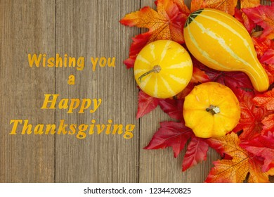 Happy Thanksgiving greeting with gourds and fall leaves on weathered wood