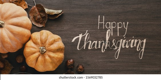 Happy Thanksgiving greeting on rustic table with pumpkins, panorama