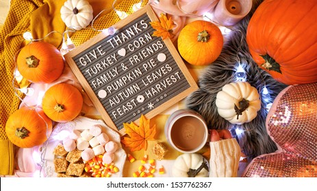 Happy Thanksgiving hygge style on trend autumn in bed flat lay with pumpkins, woman holding hot chocolate drink with plate of treats, and letter board with Giving Thanks messsage.
