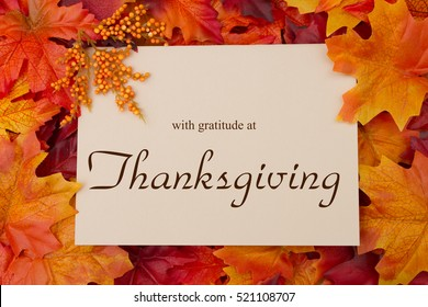 Happy Thanksgiving Message, Autumn Leaves with a beige greeting card with text with gratitude at Thanksgiving