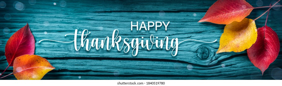 """""""Happy Thanksgiving"""" Message On Rustic Blue Harvest Table Background Decorated With Leaves"""