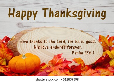 Happy Thanksgiving message, Some fall leaves, an alarm clock and wood plaque on weathered wood with text Psalm 136