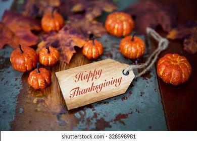 Frohes Thanksgiving auf Holzschild mit Kürbis und Blättern