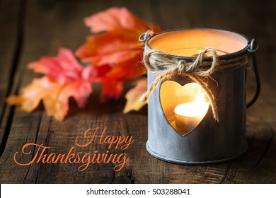 Happy Thanksgiving. Romantic shabby chic tin lantern with autumn leaves against dark rustic wooden background