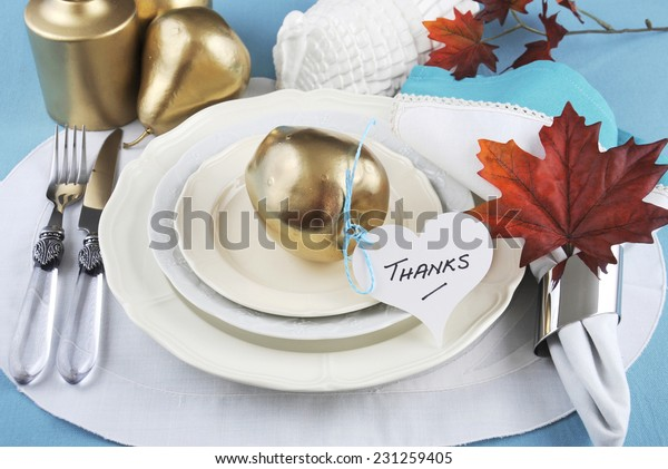 Happy Thanksgiving table place setting in pale aqua blue and white theme with gold fruit and candle