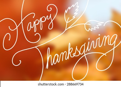 Happy Thanksgiving text design on blurred orange maple leaves
