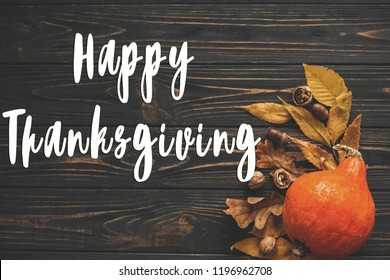 Happy Thanksgiving Text on beautiful Pumpkin with bright autumn leaves, acorns, nuts on wooden rustic table, flat lay. Seasons greeting card. Atmospheric image