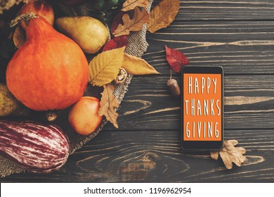 Happy Thanksgiving Text on Phone empty screen and beautiful Pumpkin with bright autumn leaves, acorns, nuts, berries on wooden rustic table, flat lay.  Seasons greeting card.