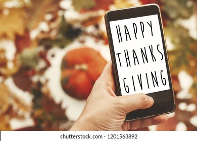 Happy Thanksgiving text on phone screen in hand at stylish autumn flat lay of pumpkin in leaves wreath.  Seasons greetings card.