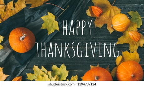 Happy Thanksgiving text with pumpkins and leaves on black wooden table background. Top view