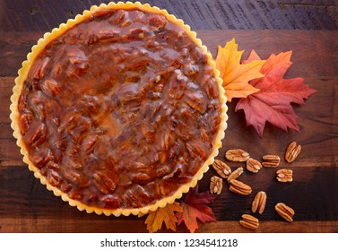 Happy Thanksgiving traditional pecan pie on vintage dark wood table and background with autumn leaves.