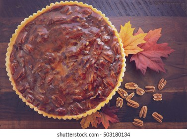 Happy Thanksgiving Traditional Pecan Pie On Vintage Dark Wood Table And Background With Autumn Leaves